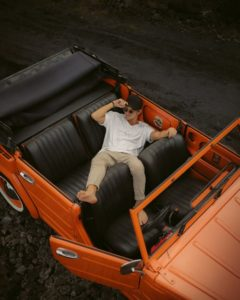 dude splayed in back of orange convertable