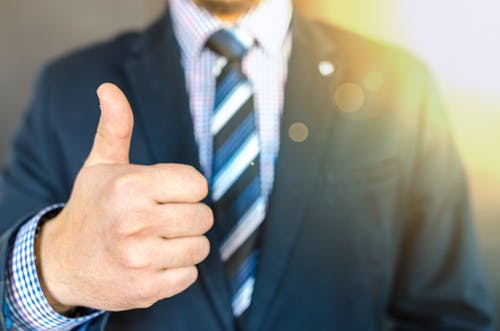 guy in a suit giving a thumbs up